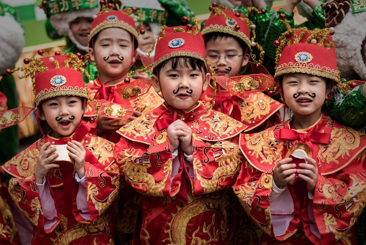 Китайские дети в красных нарядах на праздновании Нового Года