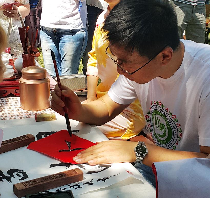 студенты из Китая пишут пожелания иероглифами на фестивале галушки