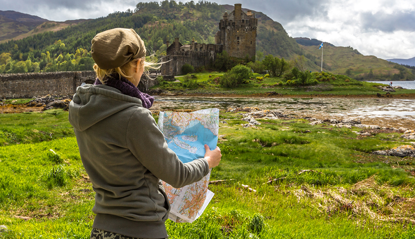 Турист у замка Эйлен-Донан в Шотландии