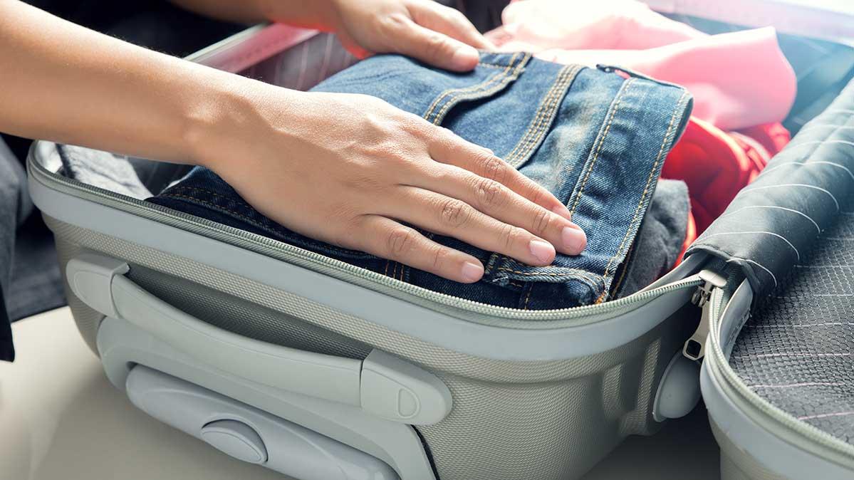Человек собирает чемодан для путешествия