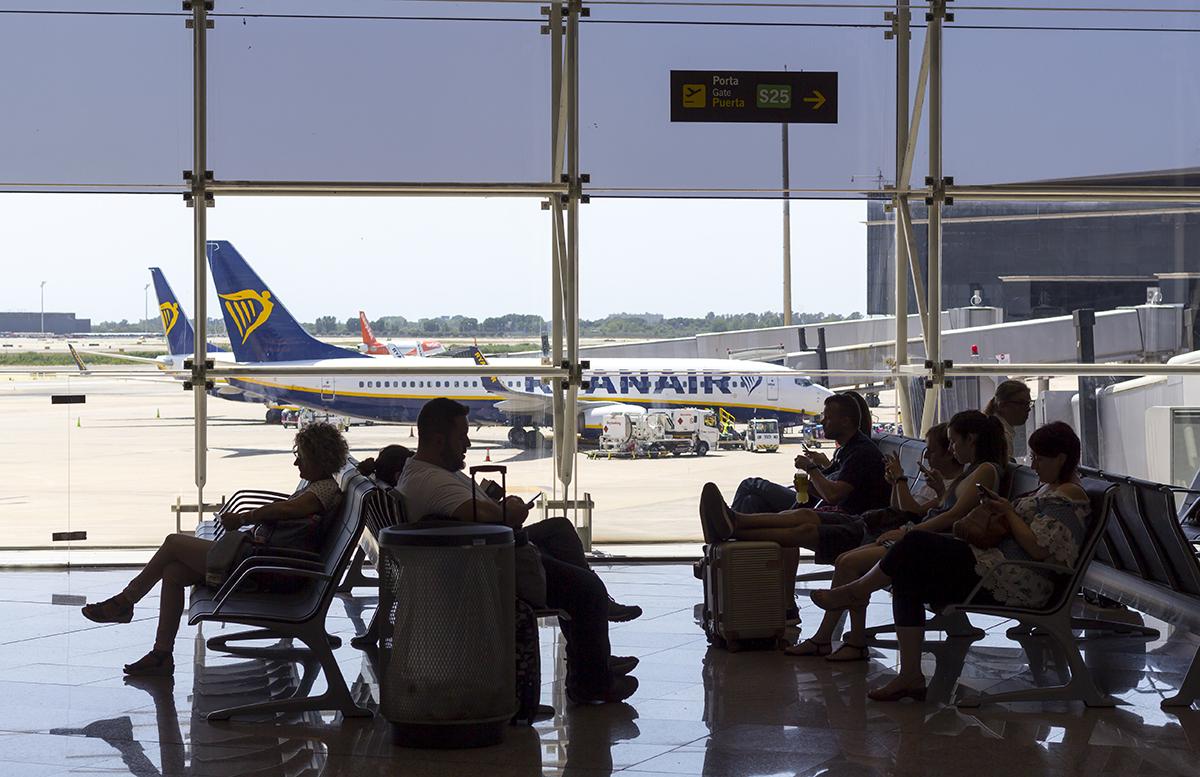 Люди в аэропорту ждут посадку на самолет